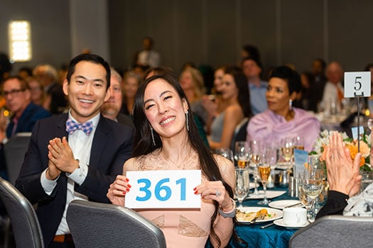 Posed smiling guest with bidder number at nonprofit gala