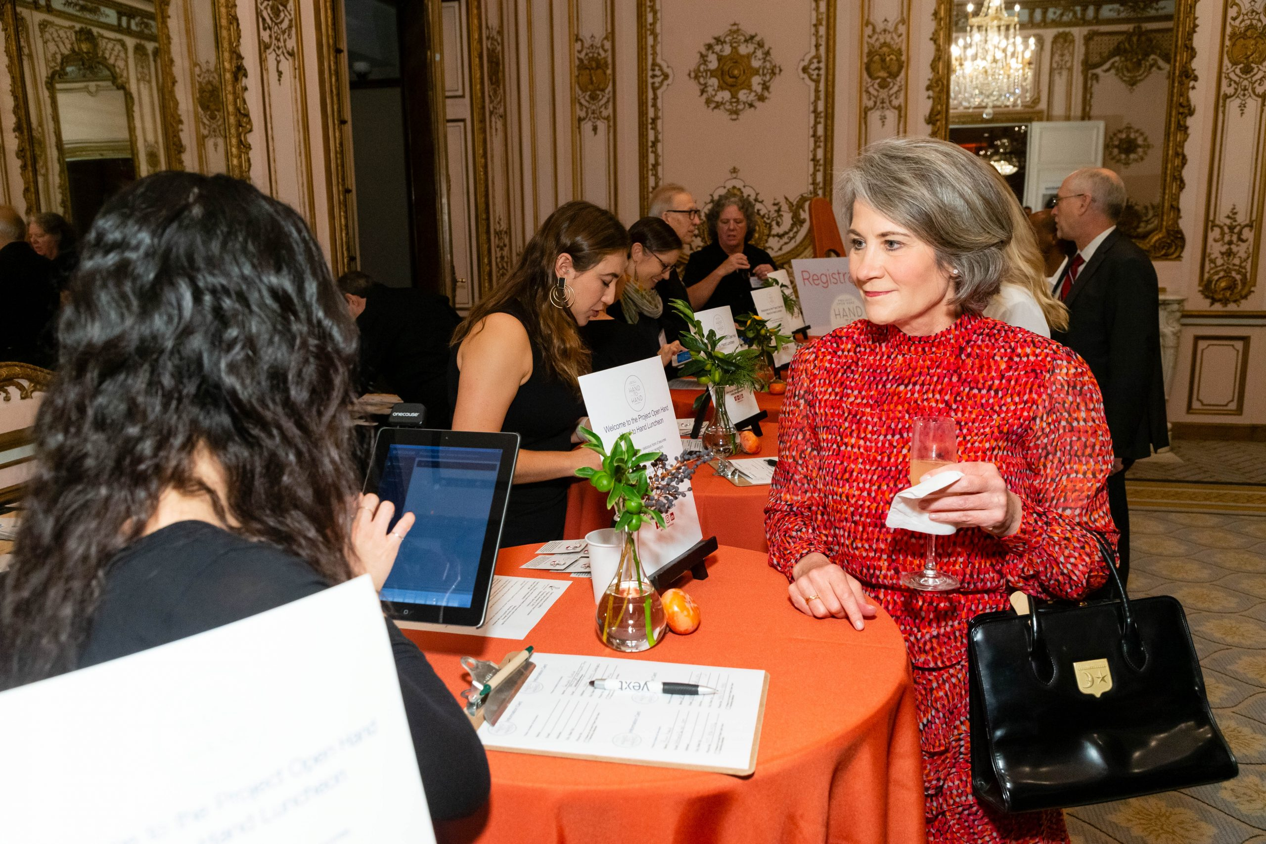 A guest in a red dress holding a drink and someone seen from their back typing on a tablet.