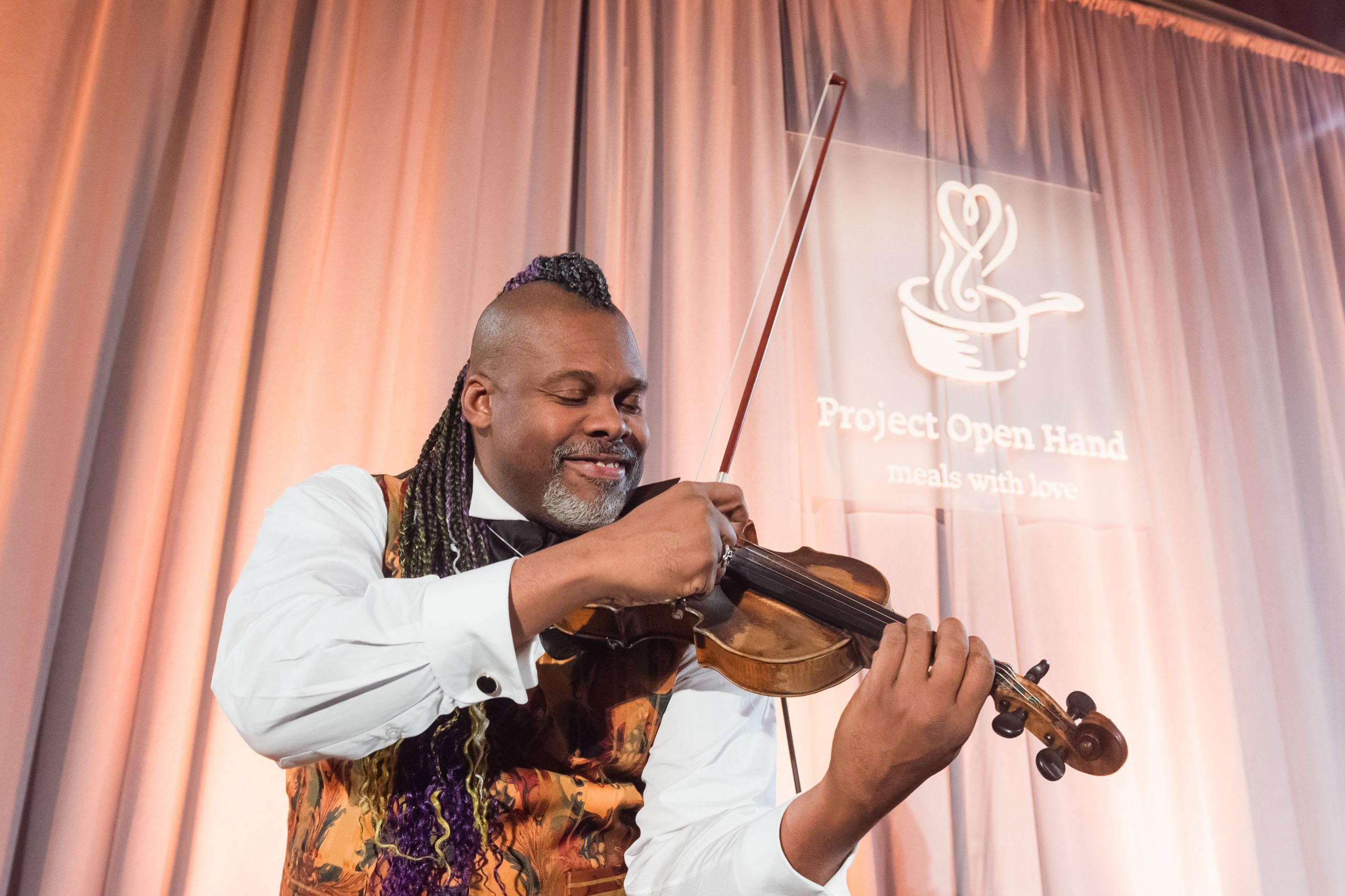 Entertainer Kippy Marks performing with a violin on stage.
