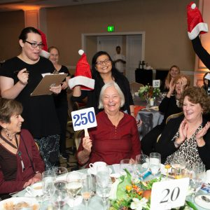 A guest bidding at Project Open Hand's Luncheon while the other guests around the guest cheer as the guest bids.
