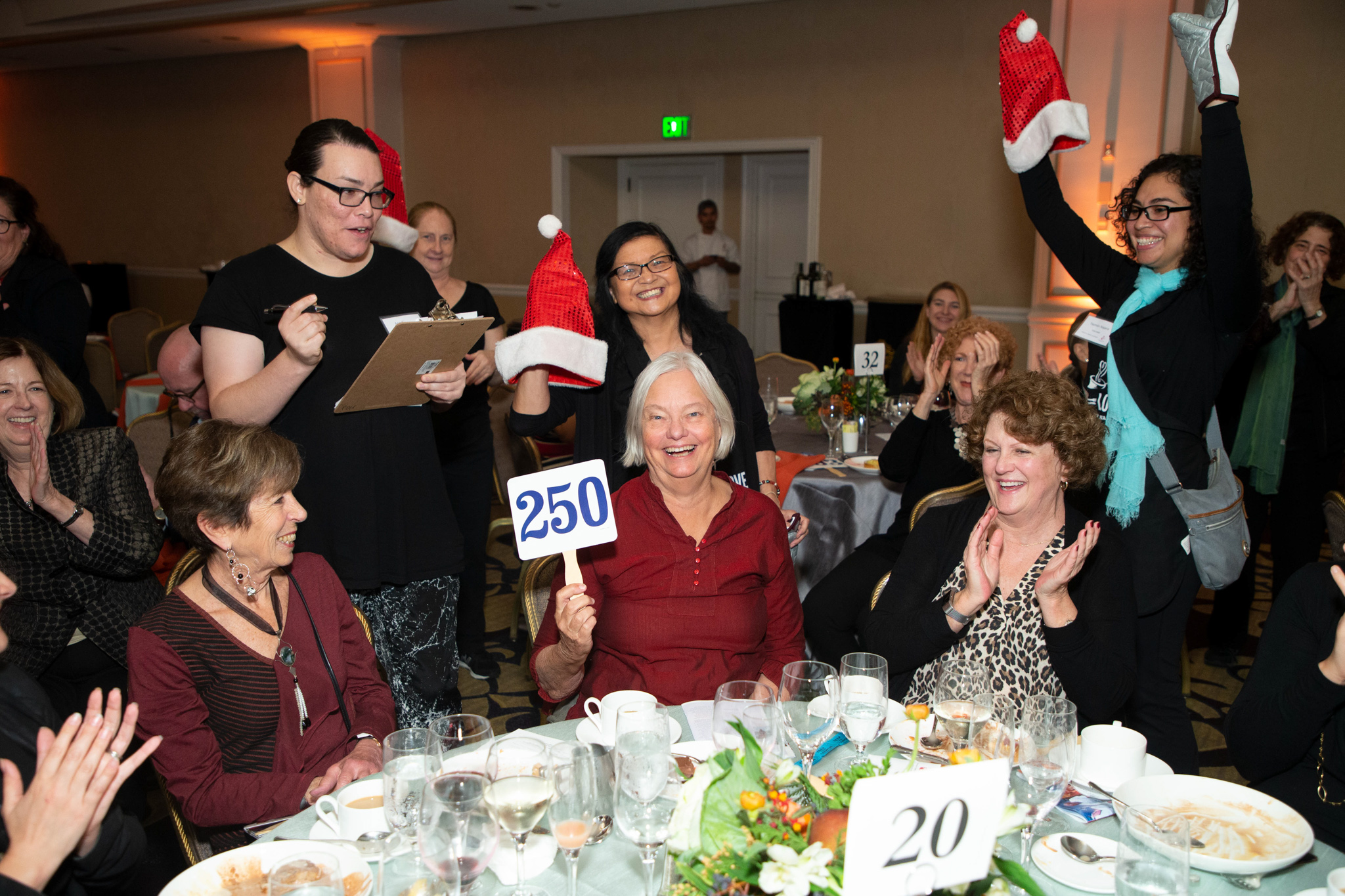 Table of attendees with bidder raising paddle