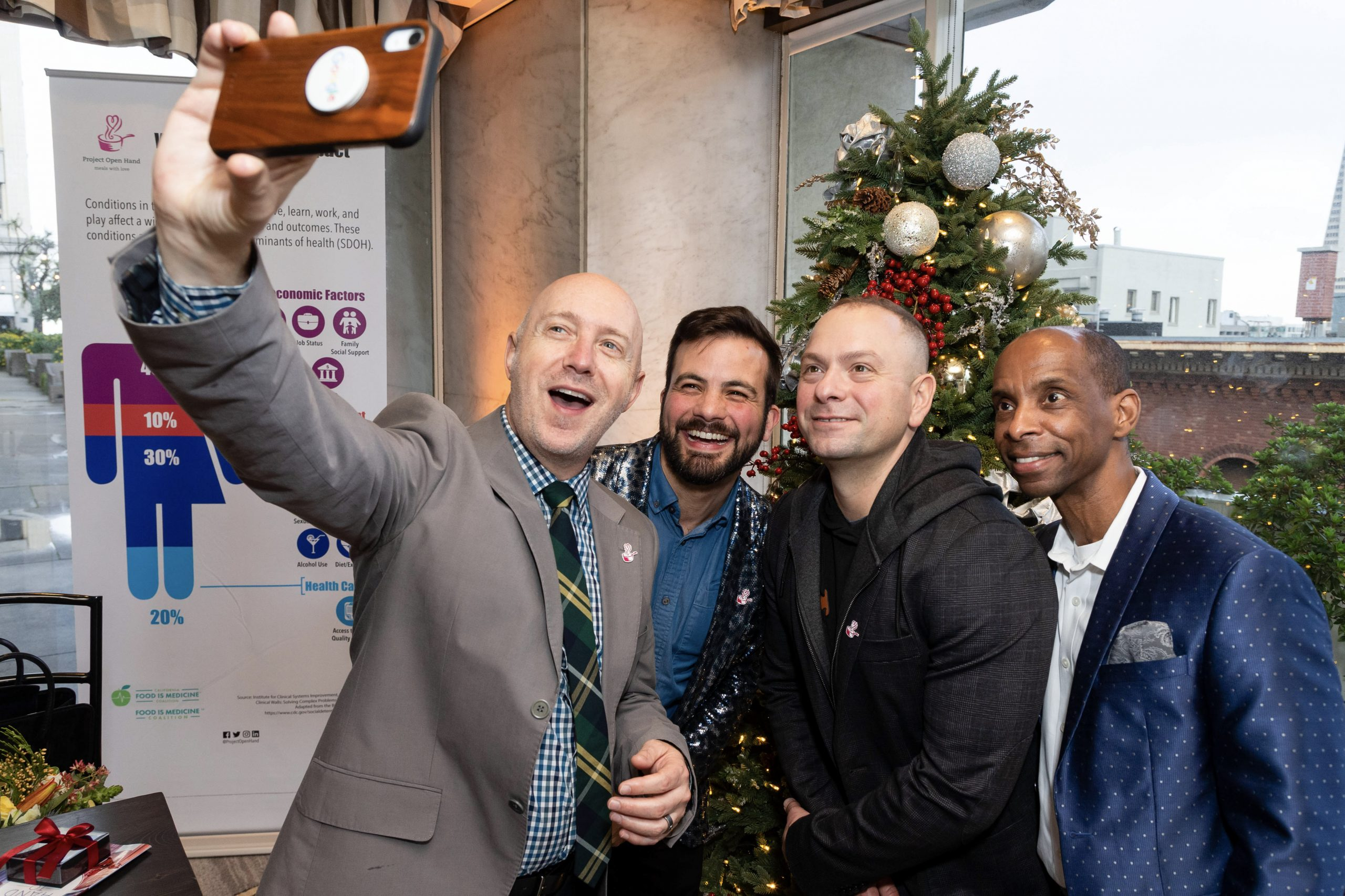 """Guests take a group """"selfie"""" with a Christmas tree and San Francisco's skyline in the background."""