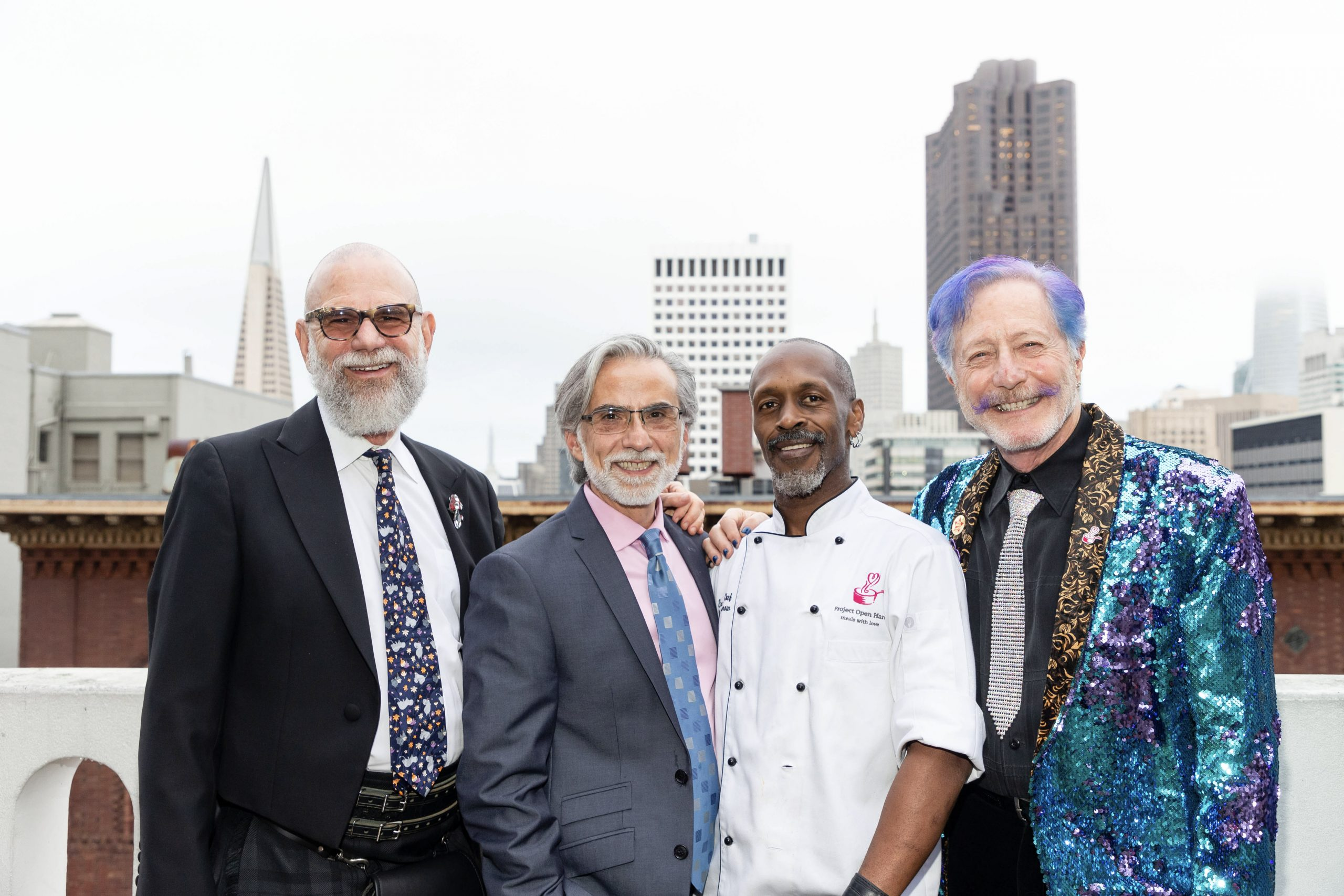 Four guests pose, with three wearing suits & ties and one wearing a chef outfit.