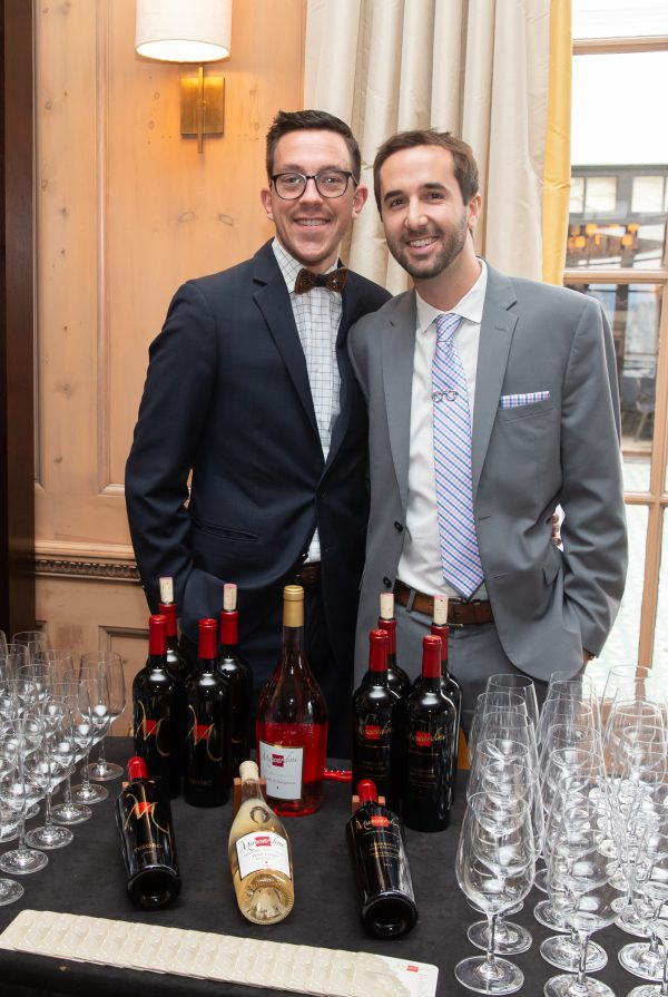 Two guests in formal attire smiling in front of a table with bottles of wine and spirits, and glasses.
