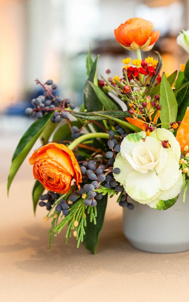 A flower decoration consisting of orange and white roses, purple and yellow flowers in a vase.