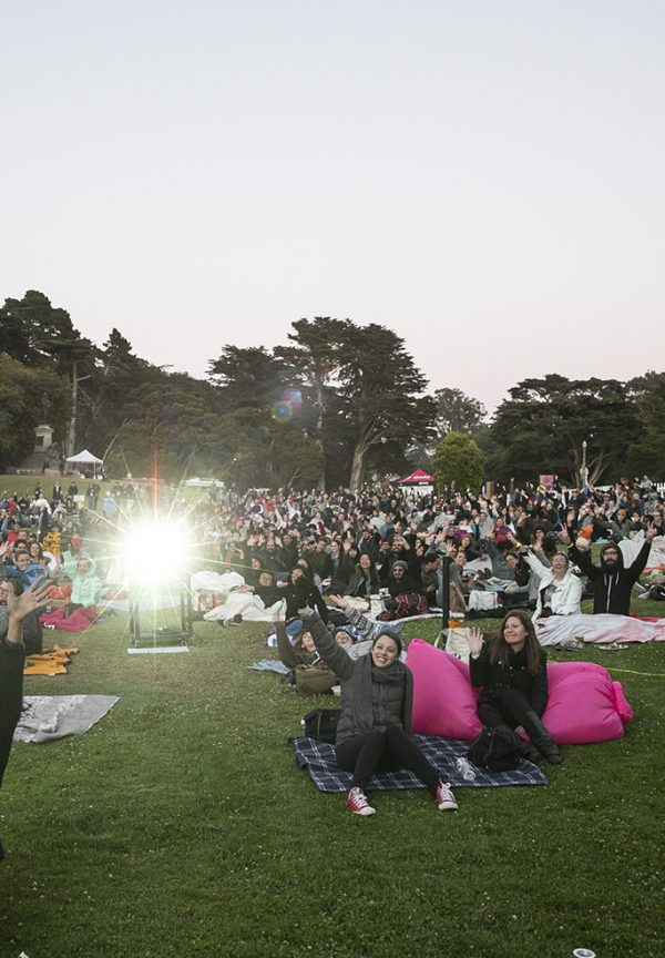 A photo of a big crowd watching a movie at a park, with bean bags and a projector beaming at dusk.