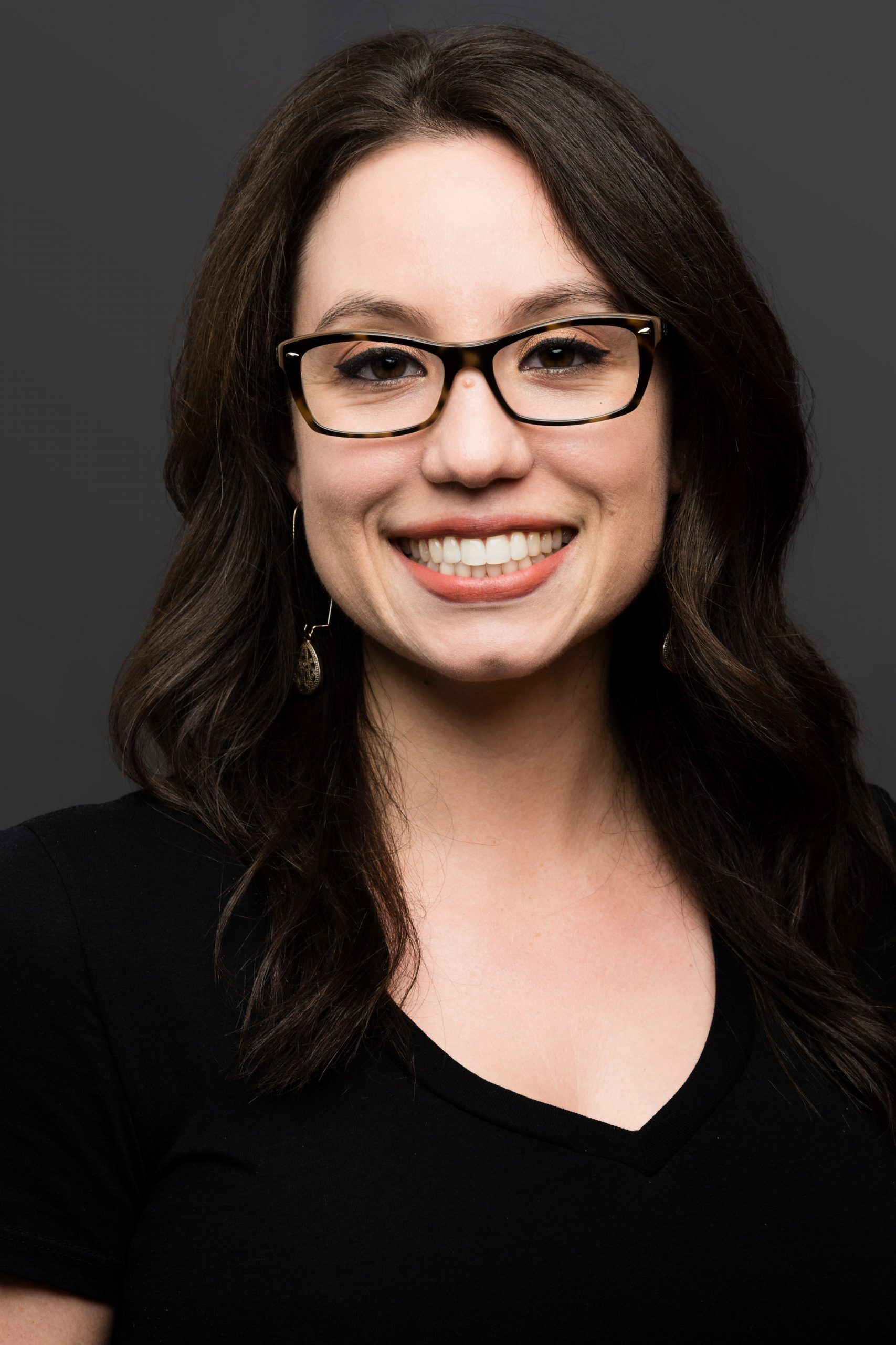 A formal headshot of Becca Bloom, with black-framed glasses, wavy hair, and a black shirt.