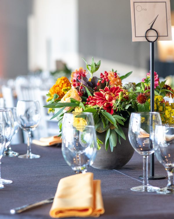 A zoomed-in table setup photo, with a vase of flowers, glasses, and yellow napkins on the table.