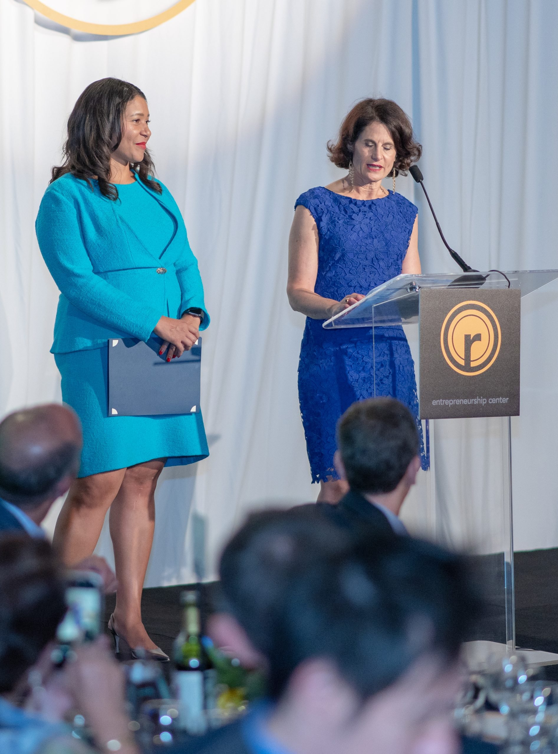 Two people in blue dresses speaking at a Renaissance Entrepreneurship Center event.