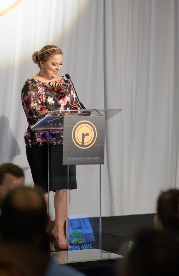 A guest with a floral top and a black skirt speaking at a podium at a formal event.