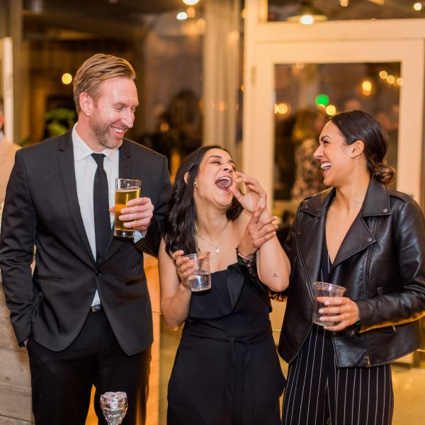 Three Masterclass Holiday Party guests in formal attire laughing while enjoying beverages.
