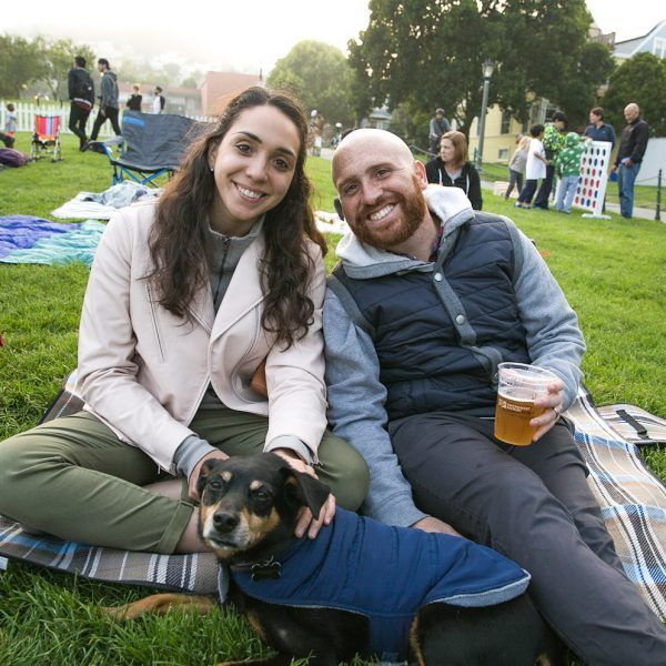 Someone enjoying a beverage and someone petting a dog, both sitting on a picnic rug.