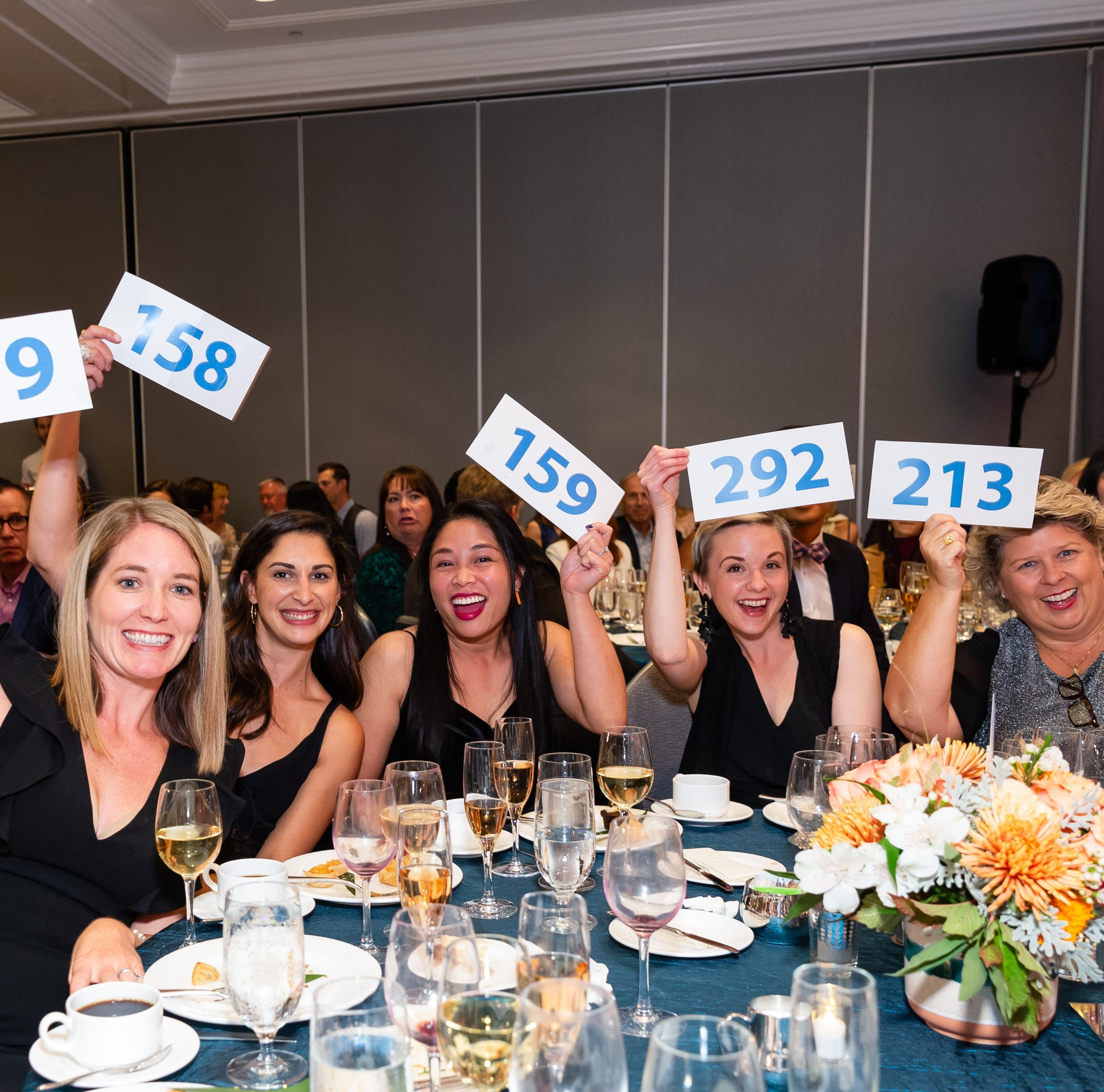 Table of women with bid paddles in the air