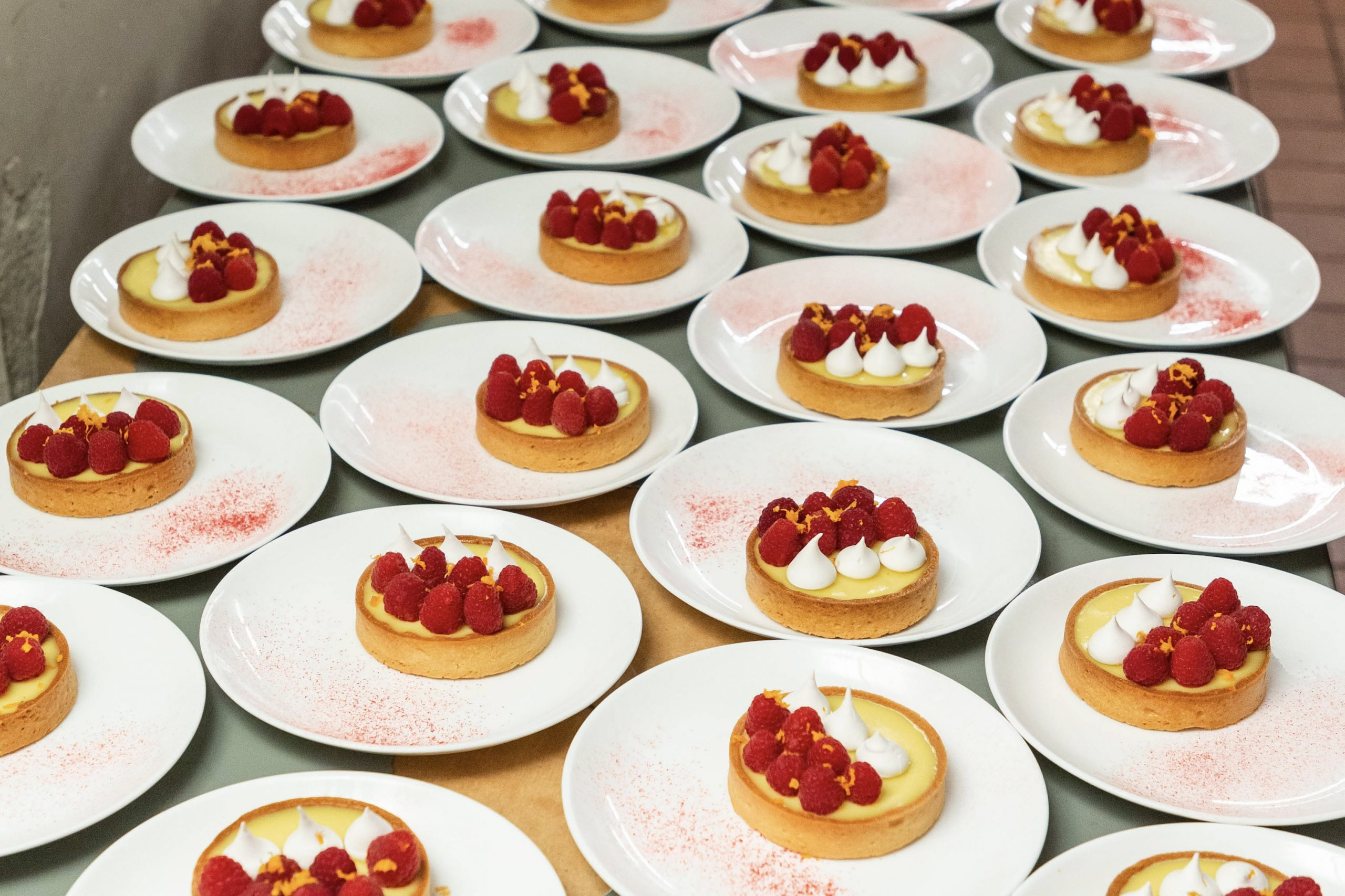 Plates of desserts that resemble lemon meringue tarts and raspberries on a kitchen counter.